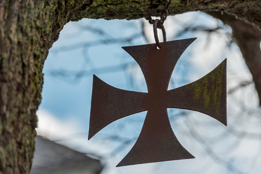 An iron cross pattée, or footed cross, hangs in a tree on the grounds of the state church in Holzhausen, Germany.