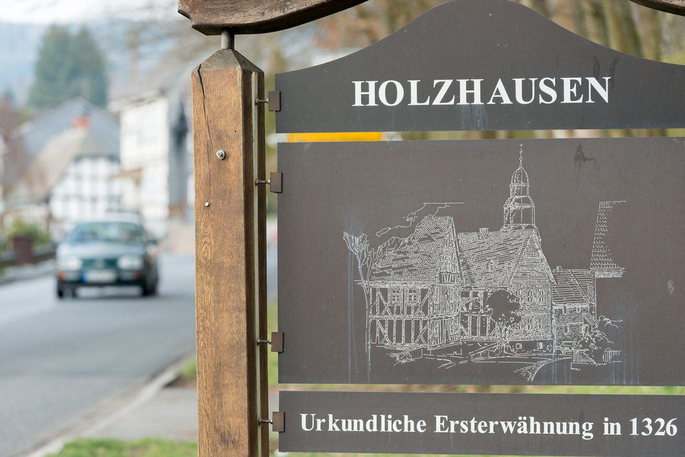 A metal and wood-timber greeting sign stands along a main road near the entrance to the village of Holzhausen, Germany. The octagonal steeple of the local state church and the half-timbered structure of the Fiester Hannes Gasthaus are featured on the sign.