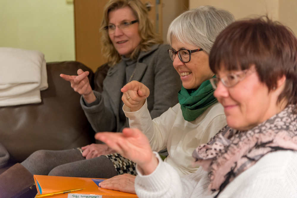 Participants in the German for Refugees course at the Wycliffe Germany offices in Holzhausen, Germany, play a name memorization game based on the language-learning techniques used in the course. As participants' names are said, others point at the person they believe to match the name.  The German for Refugees course is a train-the-trainer course designed to equip Germans to teach their language to recently arriving refugees.
