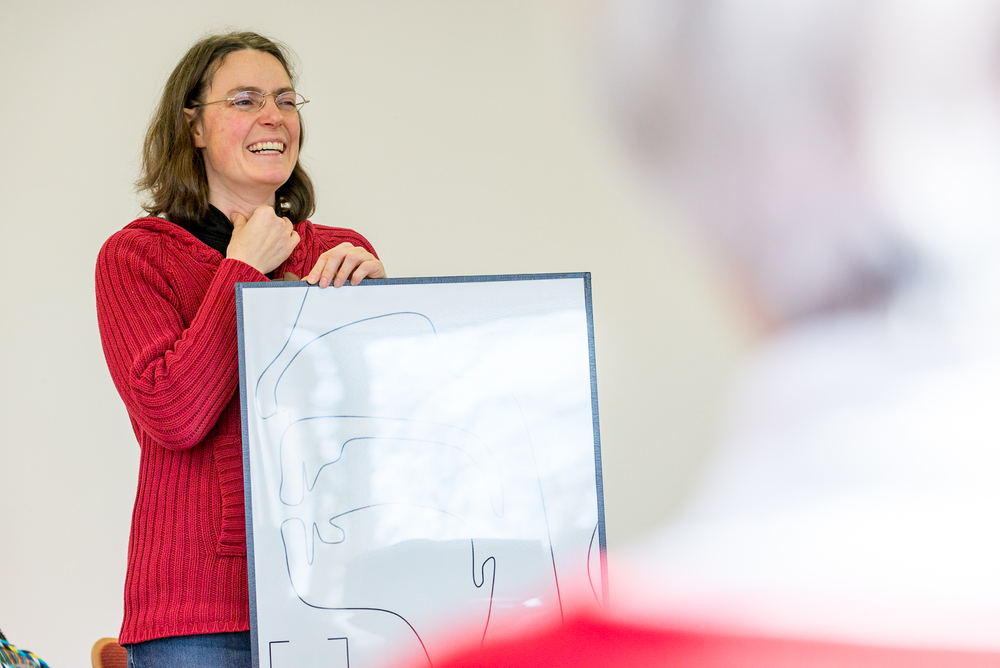 Melanie Reimer, of Wycliffe Germany, discusses phonetics with German for Refugees course participants at the Wycliffe Germany offices in Holzhausen, Germany. Melanie's mother tongue is German [deu]. The German for Refugees course is a train-the-trainer course designed to equip Germans to teach their language to recently arriving refugees.