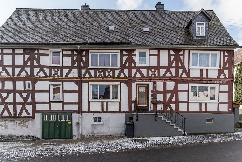 A home in Holzhausen, Germany, features a multi-story, half-timbered design, slate shingle siding and roof, as well as hand-painted references to God and Bible verses along the timbers running between the window frames and door.