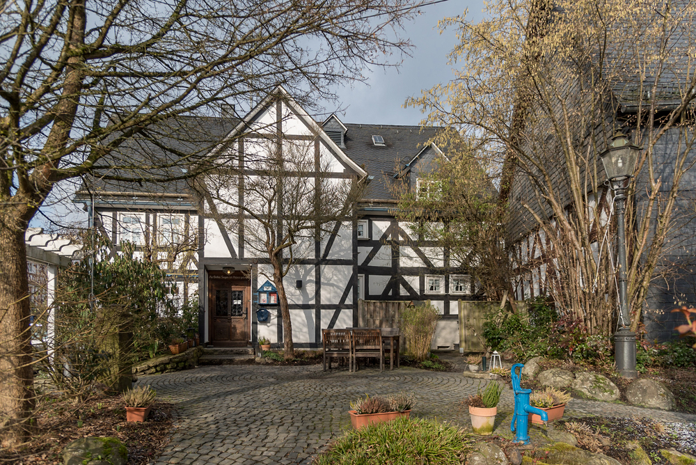 The half-timbered structure of the Fiester Hannes Gasthaus stands near the center of Holzhausen, Germany. A stone-paved courtyard lays In front of the restaurant entrance.