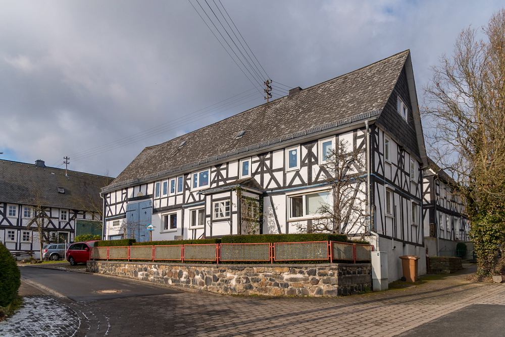 A slate-shingled, half-timbered house stands in the historic center of Holzhausen, Germany.