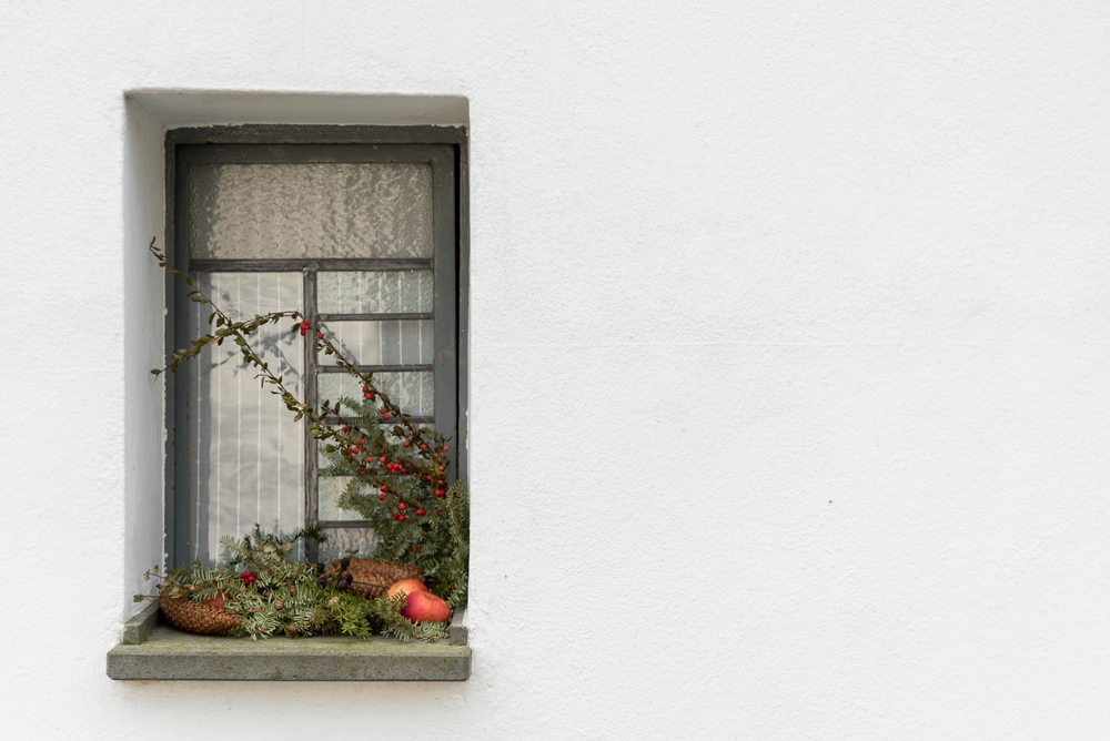 A winter greenery display rests in a ground-level window outside the state church building in Holzhausen, Germany.