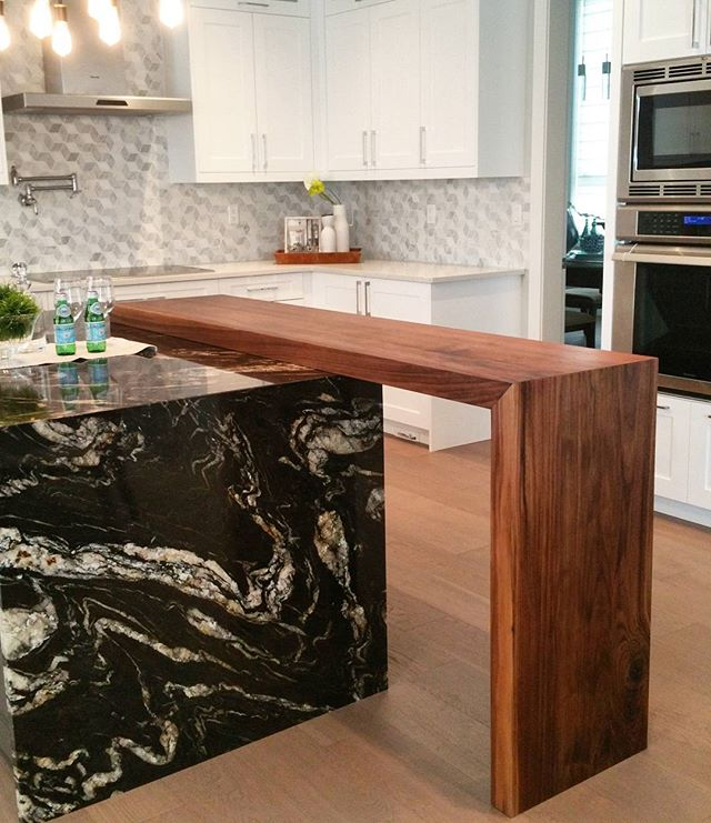 A beautiful black Walnut breakfast bar over the island granite top. #millwork #custom #home #vancityhomes #vancity #wood #exotic #walnut #cabinetmaker #woodworker #kitchendesign #kitchens #mitrecut #oilrubbed #food #realestate #milliondollarlisting