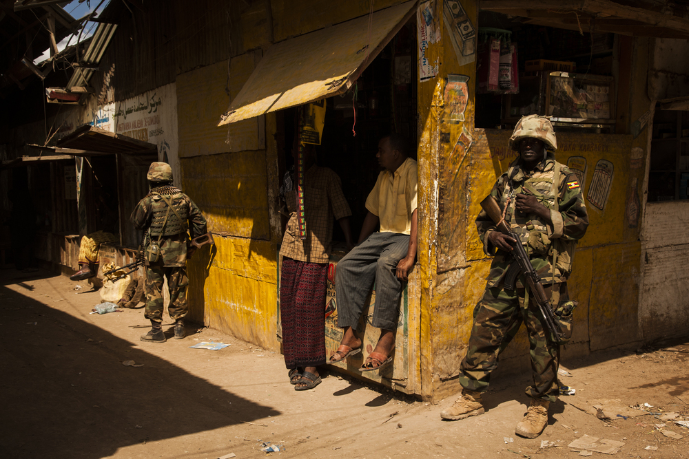 Ugandan soldiers secure the main street while out on a morning patrol in the town of Qoryooley, in Lower Shabelle, Somalia, April 29, 2014. There were few Somali soldiers to be seen in the newly captured town.  Earning $100 a month and with no training or resources, there is little incentive for the soldiers to commit to the Somali National Army.