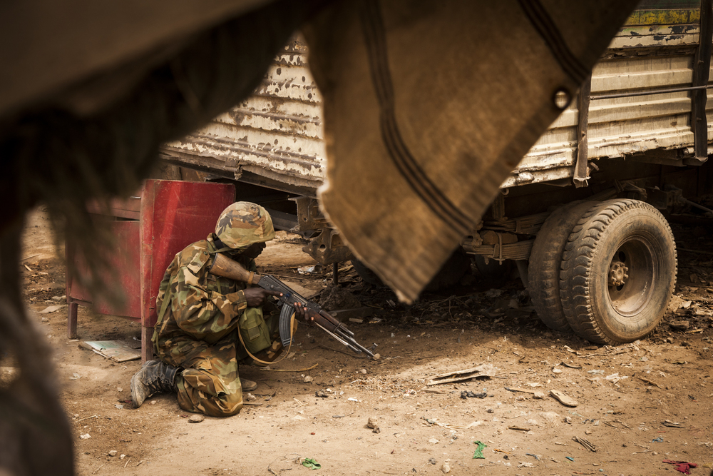 A Ugandan AMISOM soldier uses a truck for cover as he helps to secure a side street in the town of Qoryooley in Lower Shabelle, Somalia, April 29, 2014.