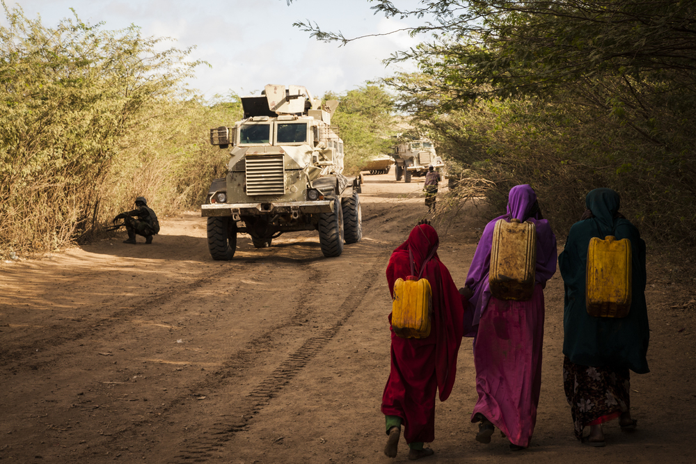 Women carry water as Ugandan soldiers patrol the road leading into Qoryooley, Lower Shabelle, Somalia, April 29, 2014. The forces use foot soldiers to search for and prevent improvised explosive devices (IEDs) from being placed along the roads.