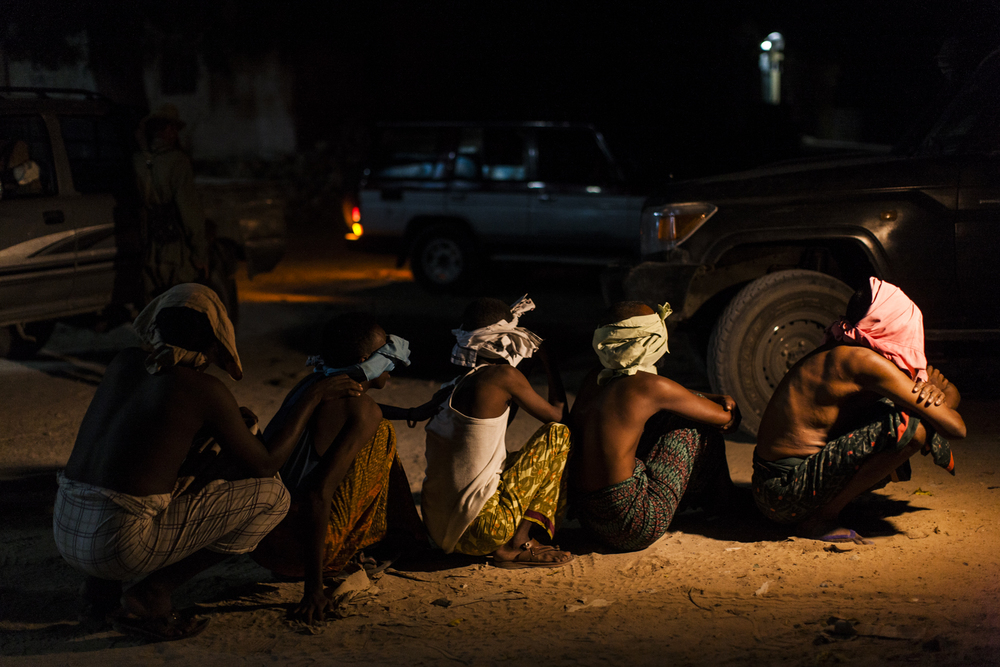 Men believed to be members of al Shabaab sit in the street after being arrested by Somali National Intelligence during a cordon and search operation in Mogadishu, Somalia, May 4, 2014.