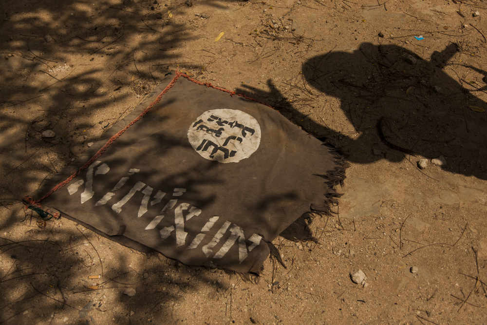 A Ugandan soldier shows off a flag which was removed from al Shabaab's base and training camp when it was taken by the Ugandan troops in Qoryooley, Lower Shabelle, Somalia, April 29, 2014.