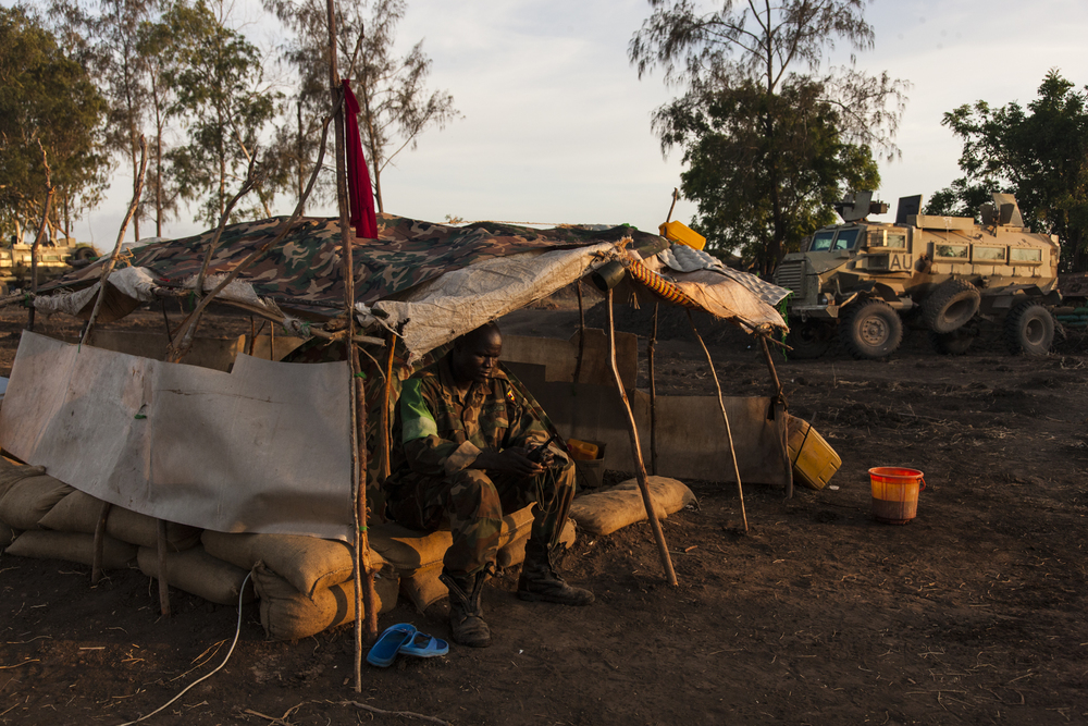 A Ugandan soldier makes a call on a satellite phone from his tent on the military base in Qoryooley, Lower Shabelle, Somalia, April 30, 2014.
