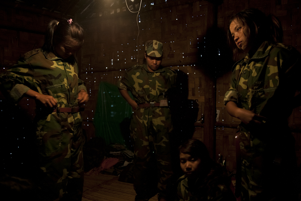 Women change into their uniforms in the room that 10 of them shared during their military training at the 3rd Brigade army base in Mai Ja Yang, Kachin State, Myanmar, May 30, 2013. While some of the women had joined out of their own interest in serving with the KIA, an equal number of women had been forcibly recruited.