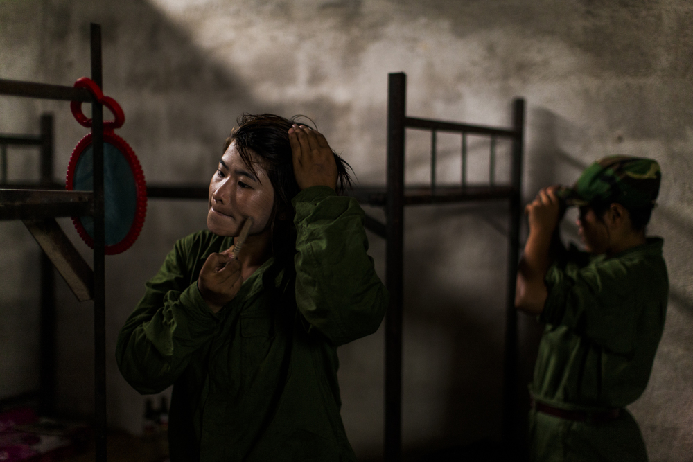 After finishing morning training a young woman applies thanaka to her face inside the women's room at the military base outside of Laiza, Kachin State, Myanmar, May 17, 2013. The 9 women shared an unlit room throughout the two-month training.