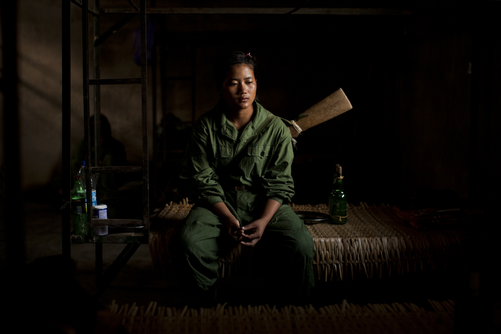 Tears roll down a young woman's face as she sits on her bed just after morning military training at the Kachin Independence Army's (KIA) 5th brigade headquarters outside of Laiza, Kachin State, Myanmar, May 21, 2013. Women in the army earn 10,000 Kyat per month (about 10 USD) and often once they have joined may only be discharged for the purpose of marriage.