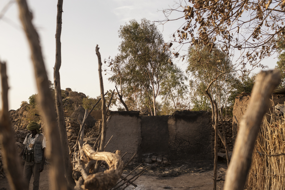 An SLA-AW soldier walks past the remains of one of many homes that were burnt during a government attack a week earlier on Koi in Central Darfur, Sudan, March 2, 2015. All of the residents have abandoned the town and only come back brifely in search of their belongings.