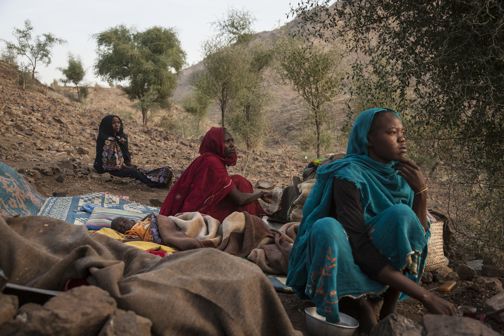 Internally displace woman who fled an attack on Golo wake up on the side of a mountain in Kone, Central Darfur, Sudan, March 1, 2015.