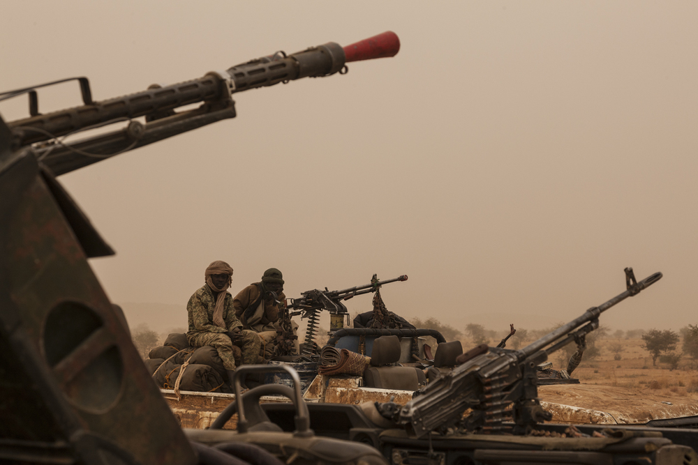 Rebel soldiers from the Sudan Liberation Army - Abdul Wahid (SLA-AW) in the middle of a sand storm in North Darfur, Sudan, February 22, 2015. The cars, weapons, and ammunition have all been taken from the government of Sudan during the ongoing fighting in the region.