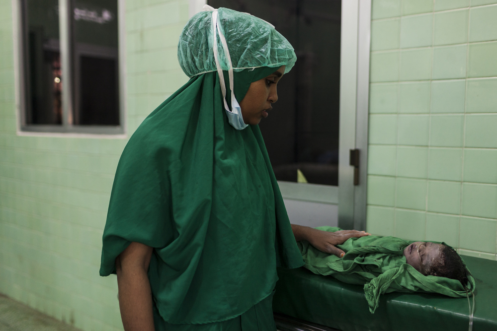 Dr. Mariam Osman Salad, age 28, monitors an asphyxiated baby boy after delivering him via Caesarian section at the Banadir Hospital in Mogadishu, Somalia, December 2, 2014.