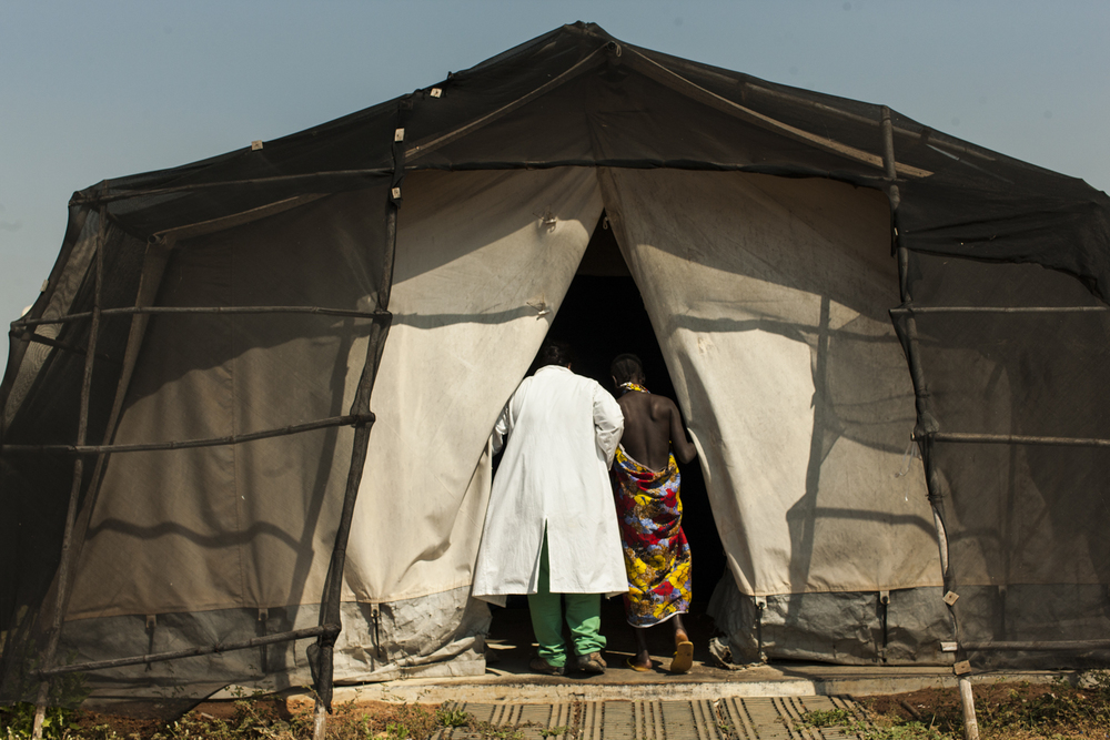 Anesthesiologist Margarita Quilala, leads a fistula patient into the inflatable operating theater at the Gogrial Health Care Center, which is run by Médecins Sans Frontières (MSF) in Gogrial, South Sudan, November 29, 2012.