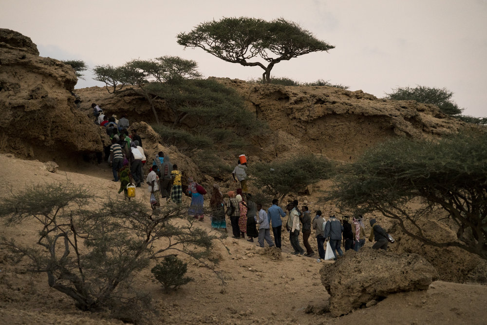 As the sun sets migrants can be seen making their way over a hill to meet the boats that will take them to Yemen from outside of the town of Obock, Djibouti, January 12, 2016.