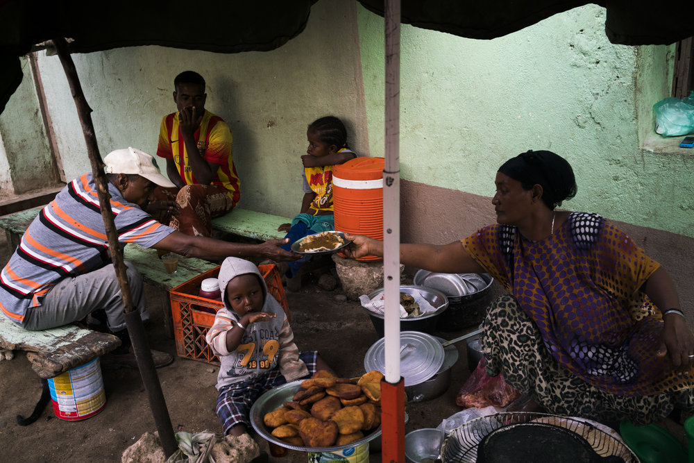 A woman serves breakfast from her shop, while her children sit close by on the main street of the port town of Obock, in Djibouti, January 14, 2016.