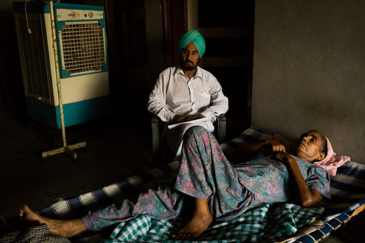 Mohinder Kaur, 48, whose two sisters also had cancer, and who is recovering from cancer for the second time, rests in her home with her husband watching over her in Mari Mustafa, Punjab, India, September 30, 2016.