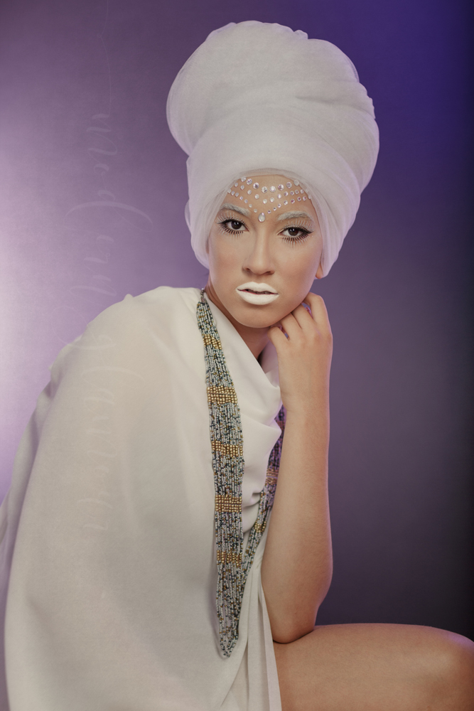 White lipstick, white head wrap, white fabric and a beaded necklace to go with a beaded brow.