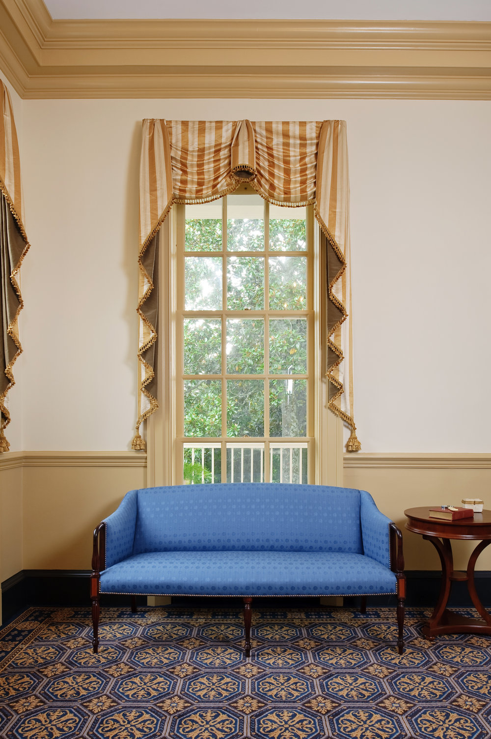 The Sheraton settee is covered in a vibrant cobalt blue, reproduction of a horsehair fabric by Brunschwig et Fils. The traditional window treatment is in a Scalamandre silk.