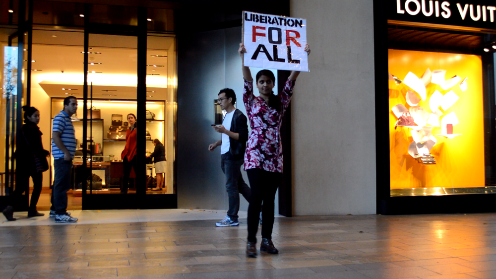 "DxE activists suddenly freeze inside of a Louis Vuitton store, to convey the message, ""STOP THE VIOLENCE."""