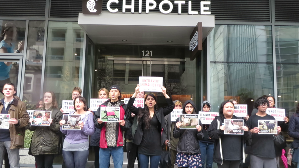 San Francisco protesters stand in front of the largest Chipotle in the city.