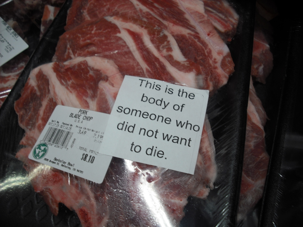 "A package containing animal flesh has a sticker on it that reads ""This is the body of someone who did not want to die."""