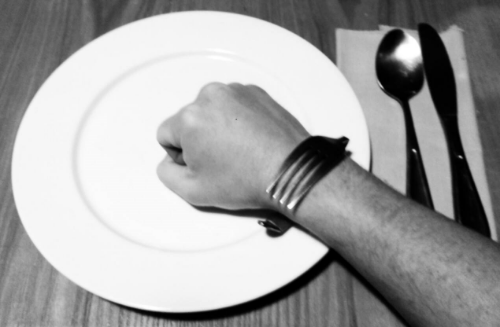 A Liberation Band (i.e. a bent fork) adorns a wrist, while a clenched fist sits atop a plate. Next to the plate is a napkin with a spoon and knife.