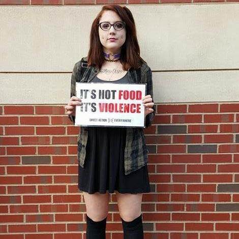 "Keira Devine, organizer for Direct Action Everywhere Philadelphia, holding an ""It's Not Food, It's Violence"" placard."
