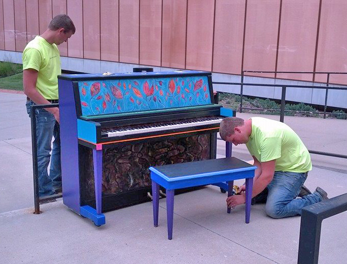 Workers installing the piano at the Central Des Moines Public Library