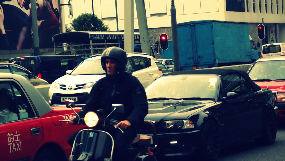 Bloke on a scooter negotiating heavy traffic on Connaught Road in Central District