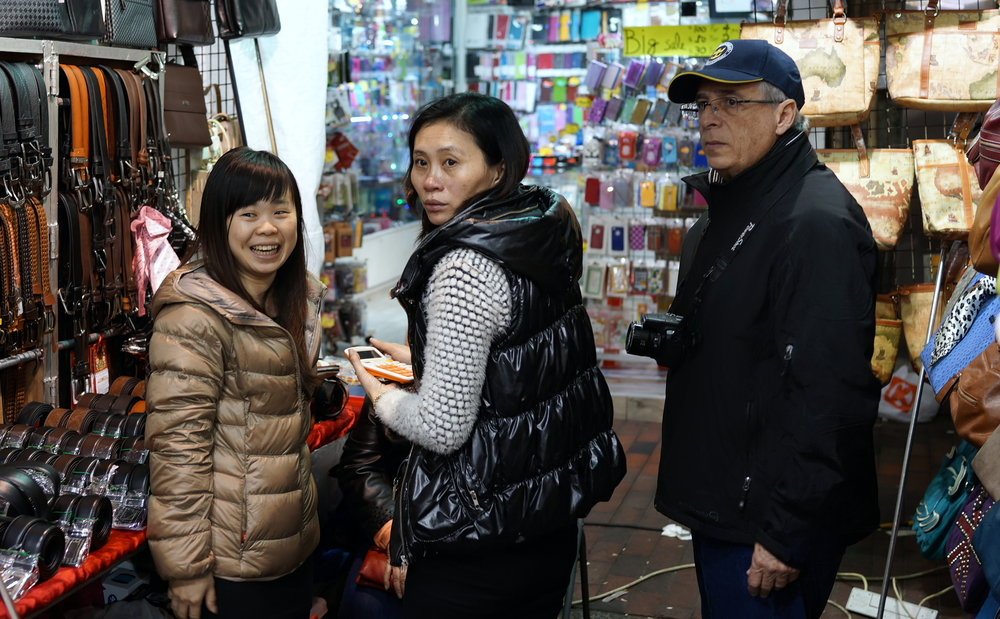 Santiago and Yami purchasing belts in the Temple Street Night Market