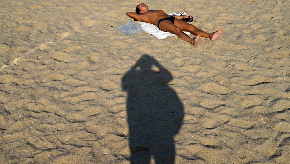 That's my shadow actually and it is a bag that makes look like I am 400lbs!! the chap catching the rays is lying on Cheung Chau Beach near the Miami Resort.
