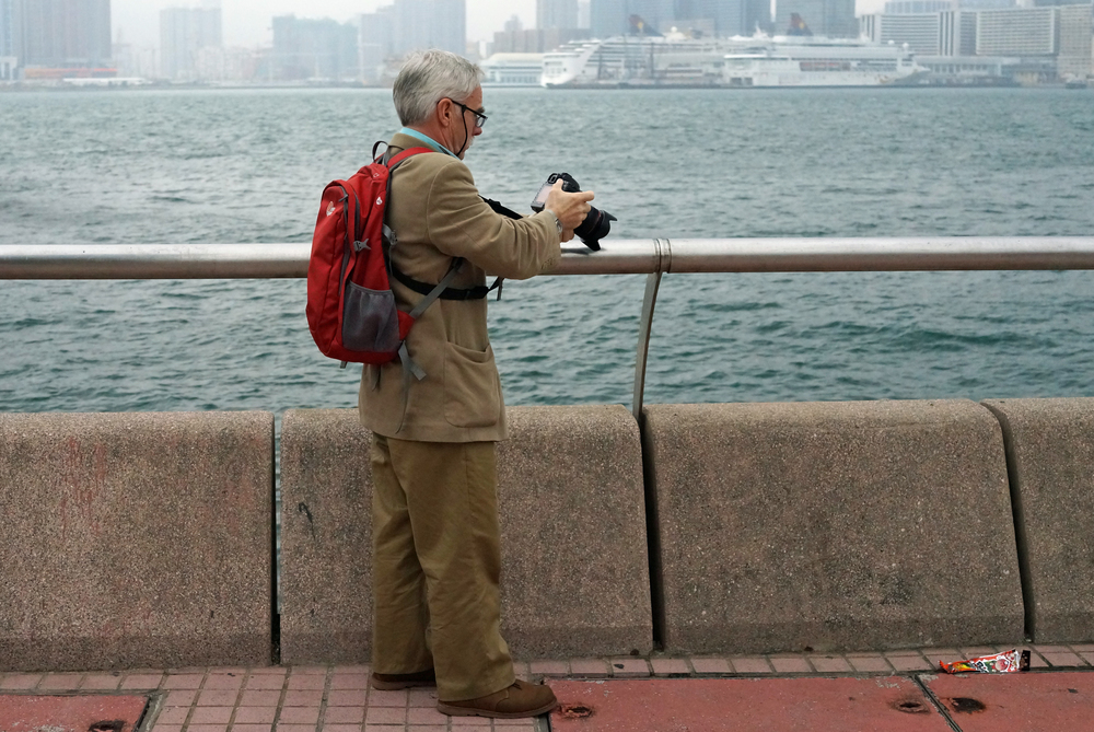 A tourist taking pictures next to the Star Ferry on Hong Kong Island