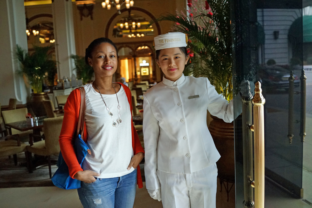 Meet Leanne, Leanne had just a few short hours in Hong Kong and here she is with the Bell Girl (!) at the famous Peninsula Hotel