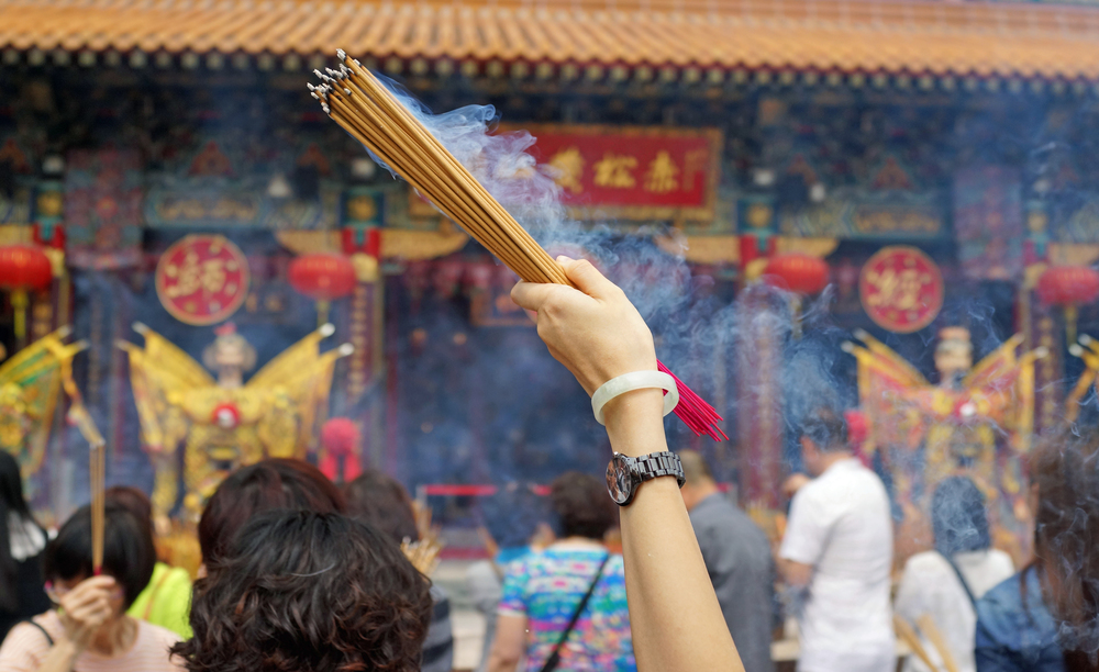 A devotee waving incense at the amazing Sik Sik Yuen Wong Tai Sin Temple