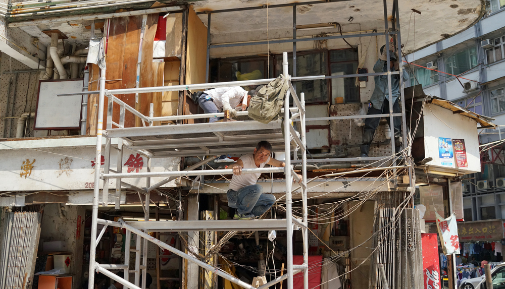 Three workmen repairing and renovating a dodgy building in Sham Shui Po in Kowloon.