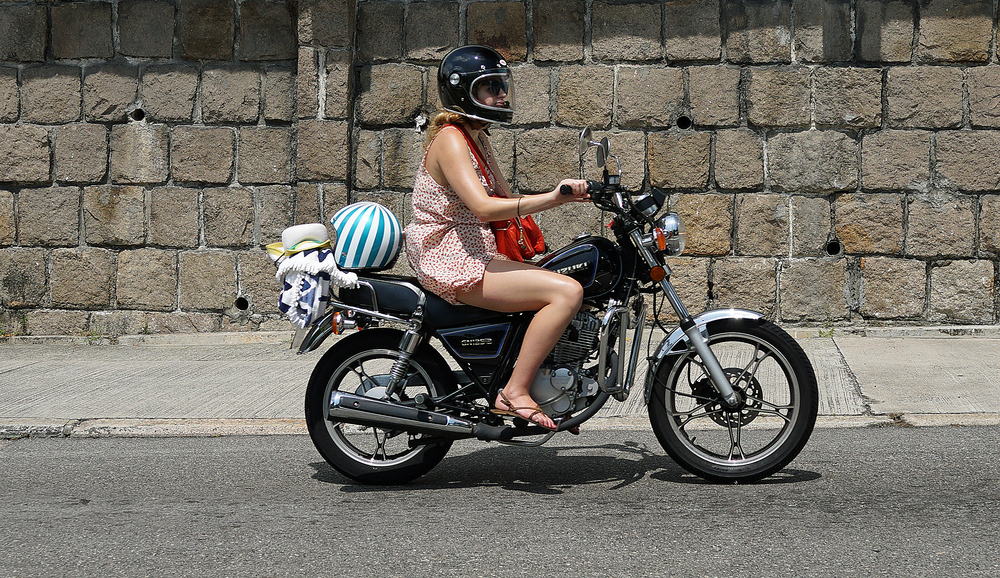 I am seeing more and more young ladies riding motorbikes (as opposed to the more traditional scooters) looks like this young lady is off to the beach!