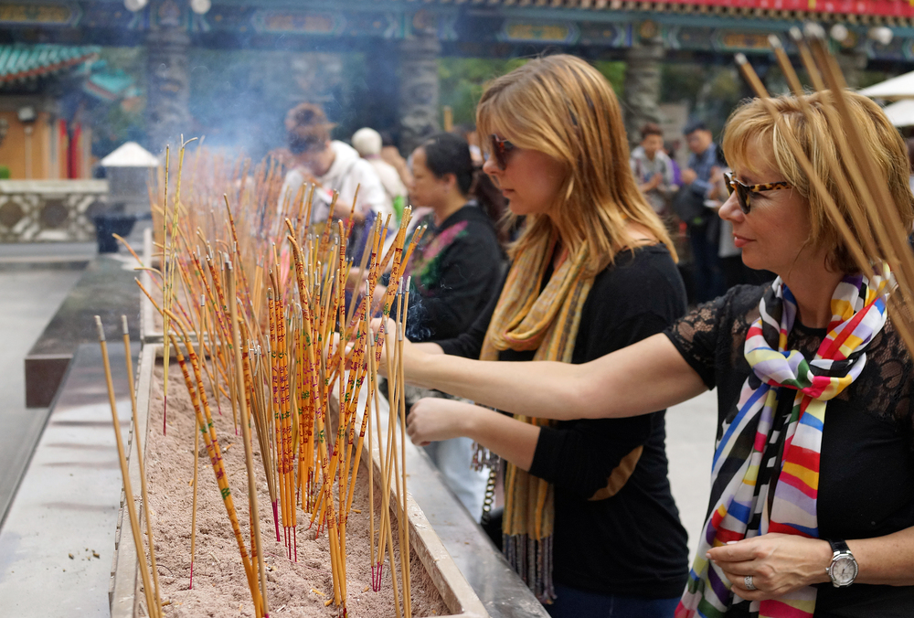 Lori and Alexis burning incense at the simply magnificent Sik Sik Yuen Wong Tai Sin Temple... -