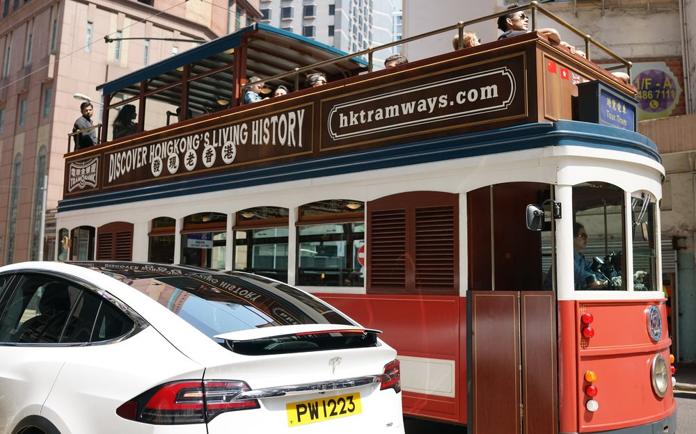 "No, the interest here is NOT the Tesla Model X but the iconic tram in the background... I have a character flaw that manifests itself when I am faced with this ""thing"" / ""mania"" in Hong for cutifying / cartoonizing iconic objects and given them stupid nicknames....  In this case I get monumentally irritated by people who refer to our iconic trams as DING - DINGS which in my old fart eyes (sorry!) makes a mockery of this vital and absolutely iconic public transport service which has been operating in Hong Kong for about 113 years, call it a tram, a street car but for god's sake stop calling it a bloody DING - DING!!  A tram ride for me is one of those essentials that all visitors must do when visiting Hong Kong, it doesn't matter whether you go on an actual working tram plying it's trade or the rather lovely 1920's replica shown in the image.. just do it."