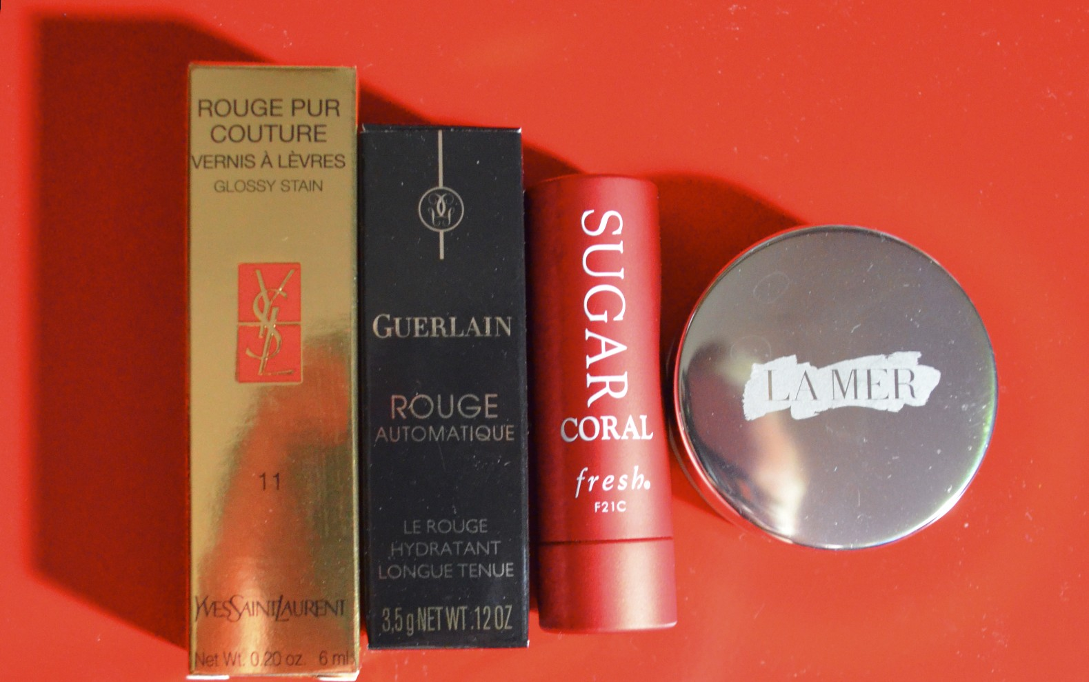 YSL Glossy Stain #11 Rouge Gouache, Guerlain Rouge Automatique 103, Fresh Sugar Coral Lip Treatment, La Mer Lip Balm
