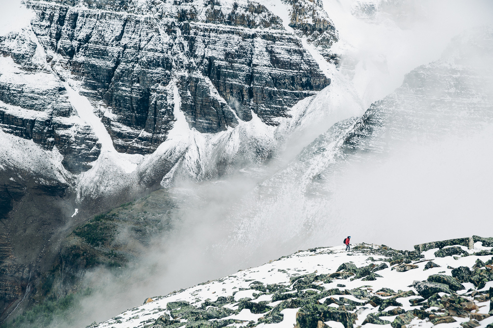 Hiker exploring the misty summit of Mount Fairview near Lake Louise, Alberta.
