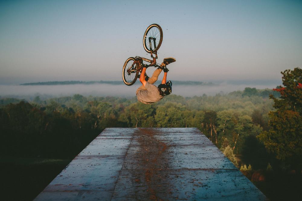 Brett Rheeder does a flip can drop off a muddy platform - Ontario Canada