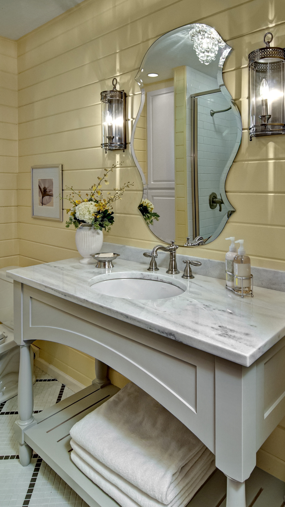 Cottage Chic Bathroom This Cottage Chic Bathroom is a perfect fit for the  yellow slat-boards, custom built cabinetry with Carrara marble top, rustic sconces and beveled mirror to swoon for.