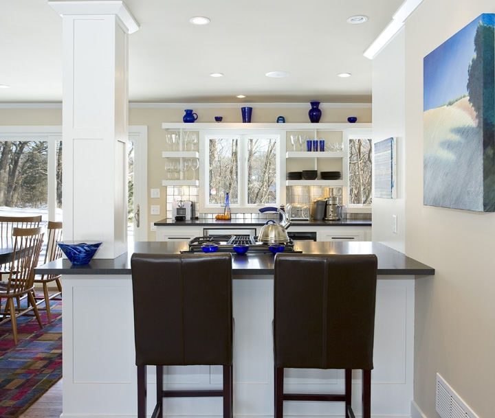 Modern Lined Kitchen  This Modern Kitchen design features open spaces, linear lines and a spacious feel with the open shelving. The punches of blue color through accessories and artwork gives the design a nice kick!