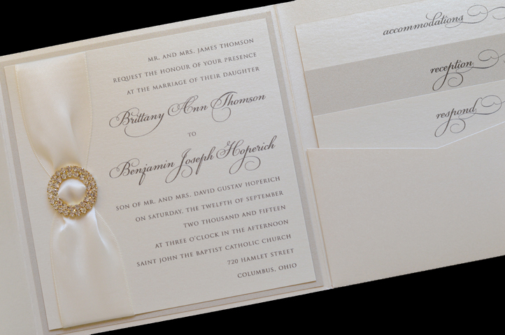 An elegant pocket invitation featuring a rhinestone brooch and alternating paper colors for the enclosures.